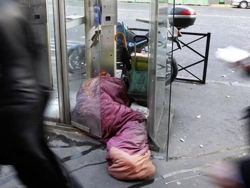 SDF malade et couché dans un duvet entre une cabine téléphonique et le trottoir